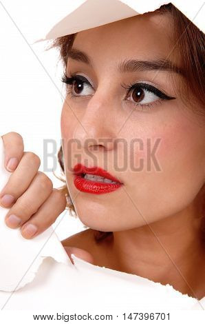 A the face of a beautiful young woman showing trough a hole in the paper with big eyes isolated for white background.