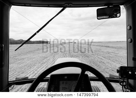A tractor window framing a field of wheat being harvested by two combines under cloudy rural black and white landscape