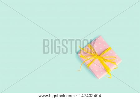 Top view of a gift box wrapped in pink dotted paper and tied yellow bow over light blue background.