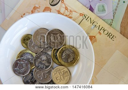 A white dish with Singaporean coins and a background of notes.