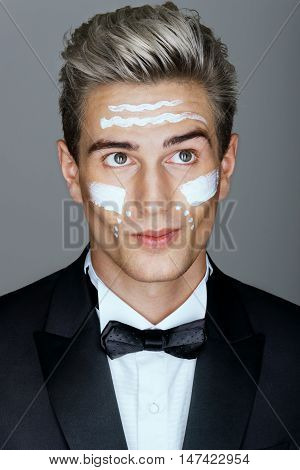 Beautiful face of imposing man with cosmetic cream on cheeks spa treatment. Photo of man in black suit on gray background. Skin care concept.
