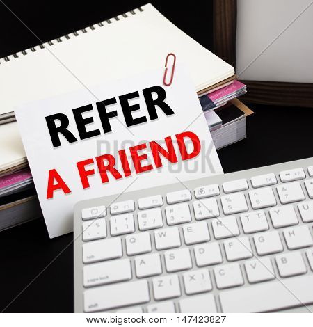 Word text Refer a friend on white paper card / business concept