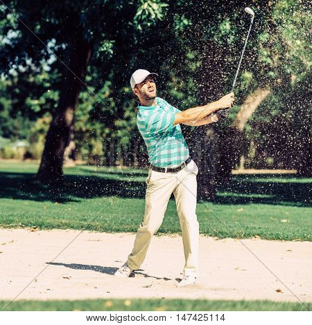 Golfer pulling ball out of sand trap, toned image, green, square image