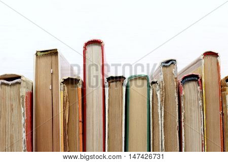 Worn various books stand on shelf of the library light top view / literature that is in demand