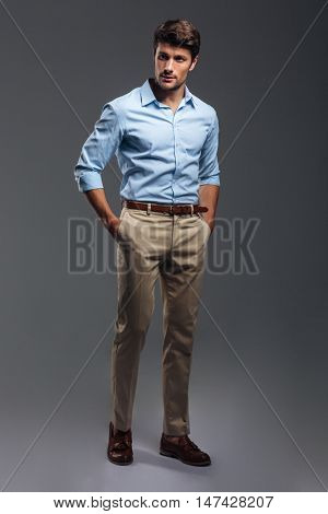 Handsome young man standing with hands in pockets isolated on a gray background