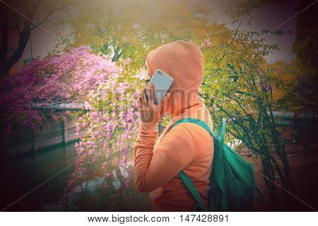 Asian woman using her mobile phone in the garden