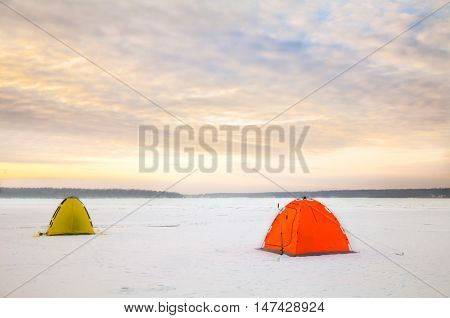 Bright tents camping of the expedition on the ice of the Northernat sunset. Wild adventure tours and trekking in the harsh winters of Northern nature. Courage and fortitude of traveler.