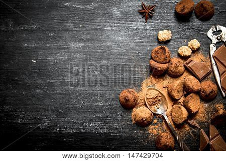 Chocolate truffles with cocoa and cinnamon. On a black wooden background.
