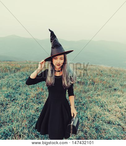 Beautiful young woman in costume of witch walking on meadow outdoor looking at camera. Toned image. Theme of Halloween and horror