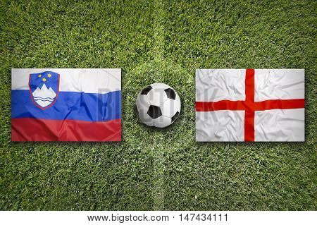 Slovenia and England flags on a green soccer field, 3D illustration
