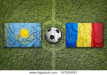 Kazakhstan and Romania flags on a green soccer field, 3D illustration
