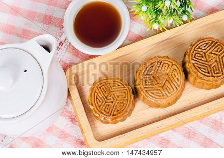 Festival moon cake and hot tea - Chinese cake on tablecloth.