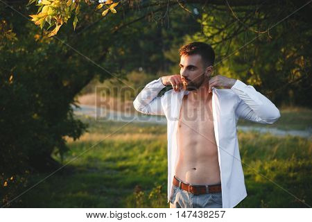 Portrait of a beautiful shirtless man in jeans in natural outdoor setting