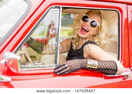 Funny woman with stylish sun-glasses driving a car