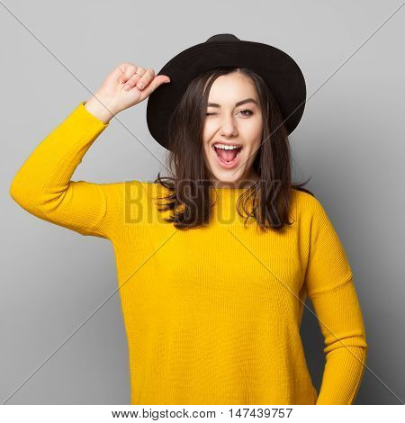 Positive cheerful young teen girl giving a wink to the camera isolated on white. Lifestyle carefree concept.