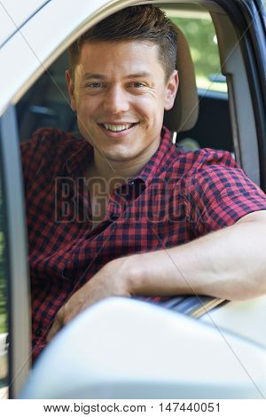 Portrait Of Smiling Young Man Driving Car