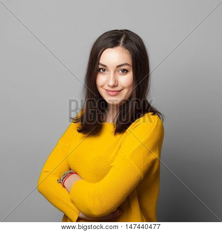 Studio portrait of happy smiling teen girl staying confident over grey background