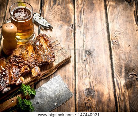 Pork ribs grilled with a meat hatchet and beer. On a wooden table.