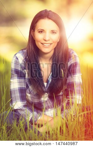 Smiling girl sitting in grass during golden hour