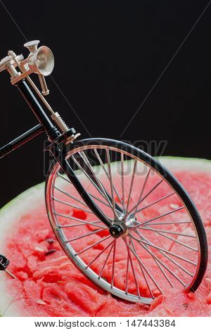 Front wheel retro vintage bicycle standing on top of a large cut in half scarlet ripe watermelon, top view, close-up, vertical