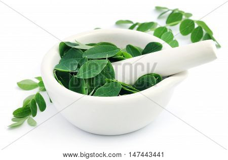 Edible moringa leaves with mortar and pestle over white background