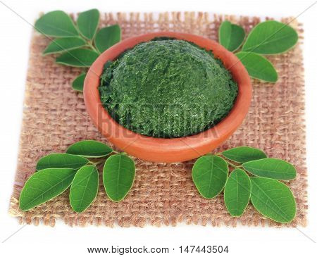 Edible moringa leaves with ground paste in a pottery