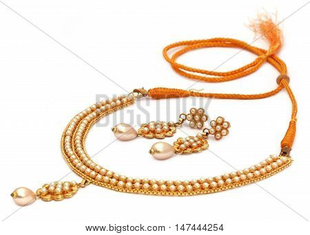 Indian necklace of gold and pearls with earrings over white background