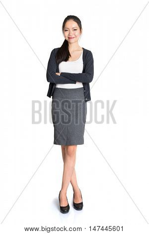 Full length portrait of young Asian female arms crossed and smiling, standing isolated on white background.