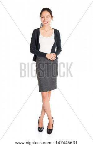 Full length portrait of young Asian girl smiling, standing isolated on white background.