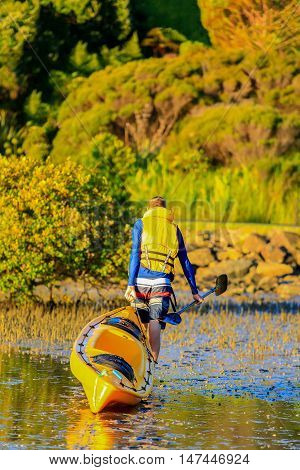 Man Carrying Kayak And Paddle In The Hand. Coromandel Coast, New Zealand