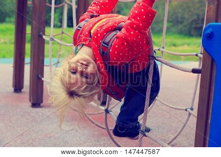 cute little girl climbing on playground after school or daycare