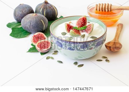 Yogurt with fig fruit pieces, near scattered sunflower seeds, laid ripe fig fruits on the fig tree leaves, honey, spoon on the white background. Yogurt with fig fruit slices and honey. Horizontal.
