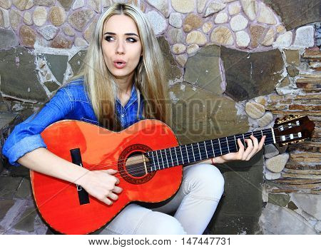 Young girl plays on the Spanish guitar on old wall background.