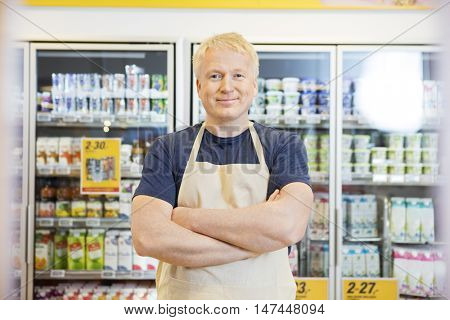 Confident Salesman Standing With Arms Crossed In Grocery Store poster