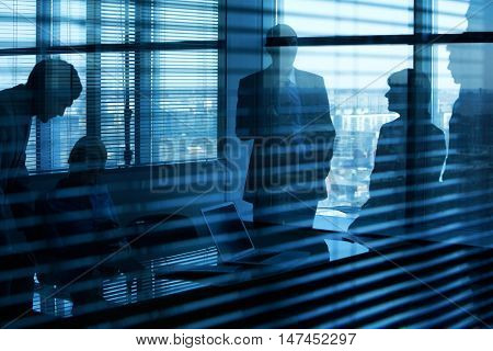 Darkened image of an office and five people in it viewed through jalousie