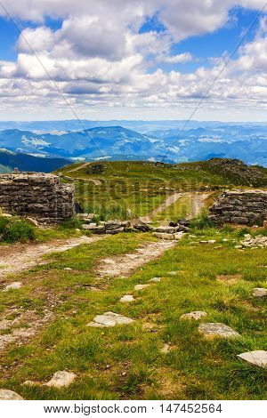 Dirt road and ruin of stone wall on the top of Pip Ivan mountain in Carpathians nature landscape Ukraine