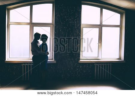 silhouette of dancing couple at a window. romantic date, couple hugging in a beautiful room with large skylights. view profile. empty space for your text