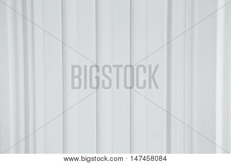 A corrugated fence of grey metal sheets with screw. Texture of metal fence with Profile decking. Internal primed side of a metal picket fence