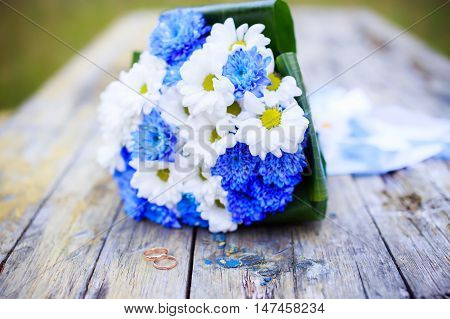 wedding still life. wedding rings and bridal bouquet of white and blue flowers on a wooden bench outdoors. selective focus