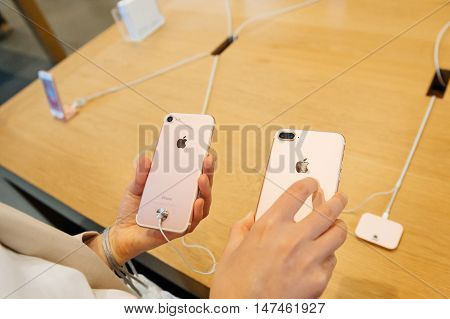 PARIS FRANCE - SEPTEMBER 16 2016: New Apple iPhone 7 being tested by woman after purchase - comparing the both iPhone 7 and iPhone 7 Plus photo camera. New Apple iPhone tends to become one of the most popular smart phones in the world in 2016