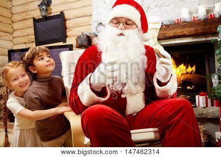 An image of Santa Claus sitting in armchair at fireplace and eating cookie with milk and two children looking at him