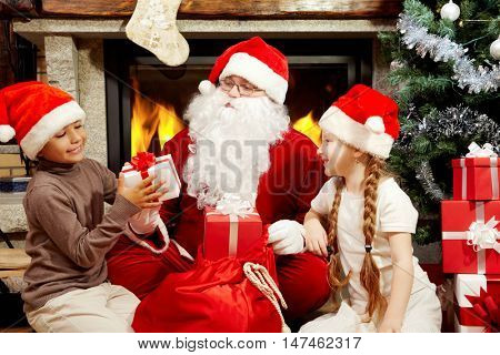 An image of Santa Claus sitting at fireplace and Christmas tree and giving presents to two children