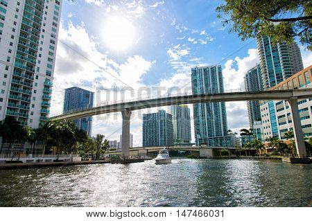 Downtown Miami along the Miami River inlet with Brickell Key in the background and yacht cruising under the bridge