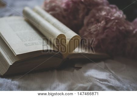 Beautiful composition with a book, pages in form of heart and peonies on the background