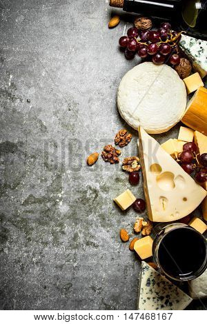 Pieces of cheese with red wine and nuts. On the stone table.