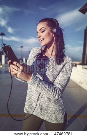 Excited woman listening music at park house in downtown searching playlist on tablet playing or messaging outdoor