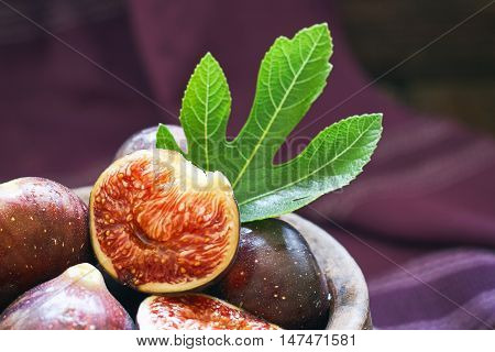 Fresh ripe black figs and fig leaf in rustic bowl on purple background. Copy space