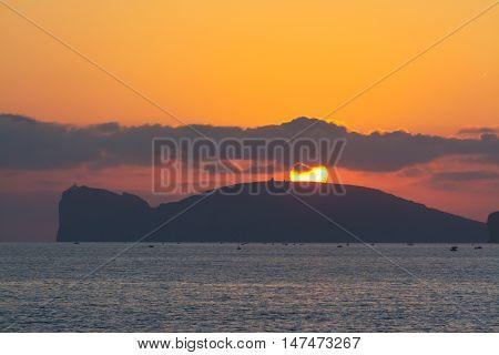 bright sun over Capo Caccia at sunset Sardinia