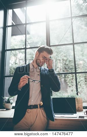 Feeling overworked. Low angle view of frustrated young man carrying eyeglasses and massaging his nose while keeping eyes closed and standing in front of big window in office
