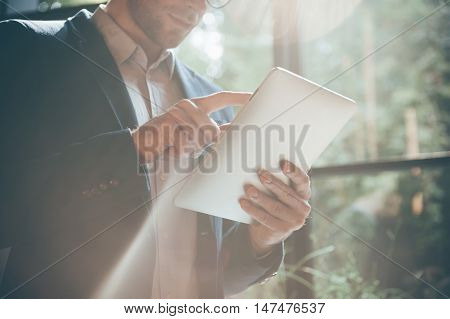 Technologies making life easier. Close-up low angle view of young man working on digital tablet while standing in front of the big window indoors